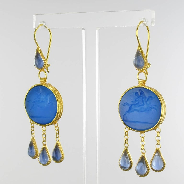 For pierced ears.  Pair of earrings in vermeil, silver and yellow gold.  Drop earrings are set by a blue intaglio on glass paste and glass crystals. The clasps are goosenecks with safety hooks.   Overall length: 6.5 cm, width to the widest: 2 cm,