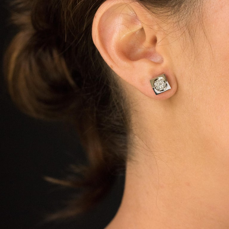 Pair of earrings in 18 carats white gold. Lovely and original earrings, they consist of a square decor with convex lines set in the center of modern brilliant- cut diamonds. The clasp is a large butterfly. Height: 8.5 mm, width: 8.5 mm, thickest