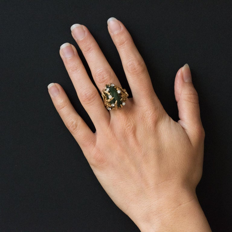 Ring in 14 karats yellow gold ring. Important ring with modernist lines is set with a nephrite jade cabochon imprisoned in a carved decor such a gnarled and asymmetrical branching. 7 brilliant-cut diamonds are set. The carving extends to the base of