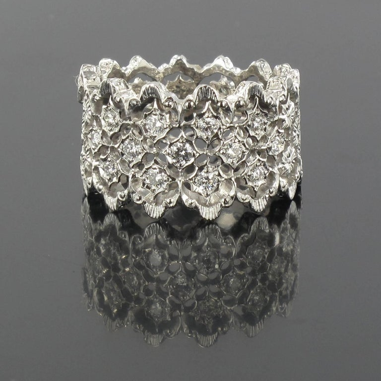 Ring in 18 karat white gold.  This wide diamond ring features white gold filigree set with 13 small brilliant- cut diamonds edged with gold filigree.  Total diamond weight: about 0.34 carat. Width: 1.3 cm Total weight: about 7.4 g. US Size : 7, Free