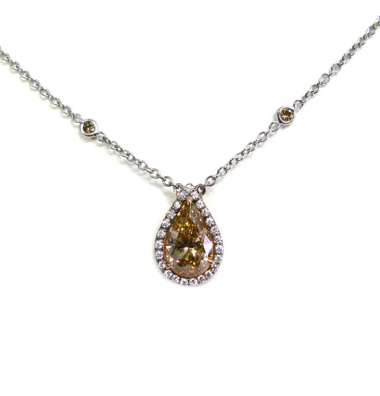 The stunning 18kt pink gold pendant features a unique GIA certified 2.35ct, Fancy Orange Brown color pear shape diamond surrounded by a 0.21ctw white round brilliant diamond pave frame and is suspended from a diamonds by the yard chain. You can wear