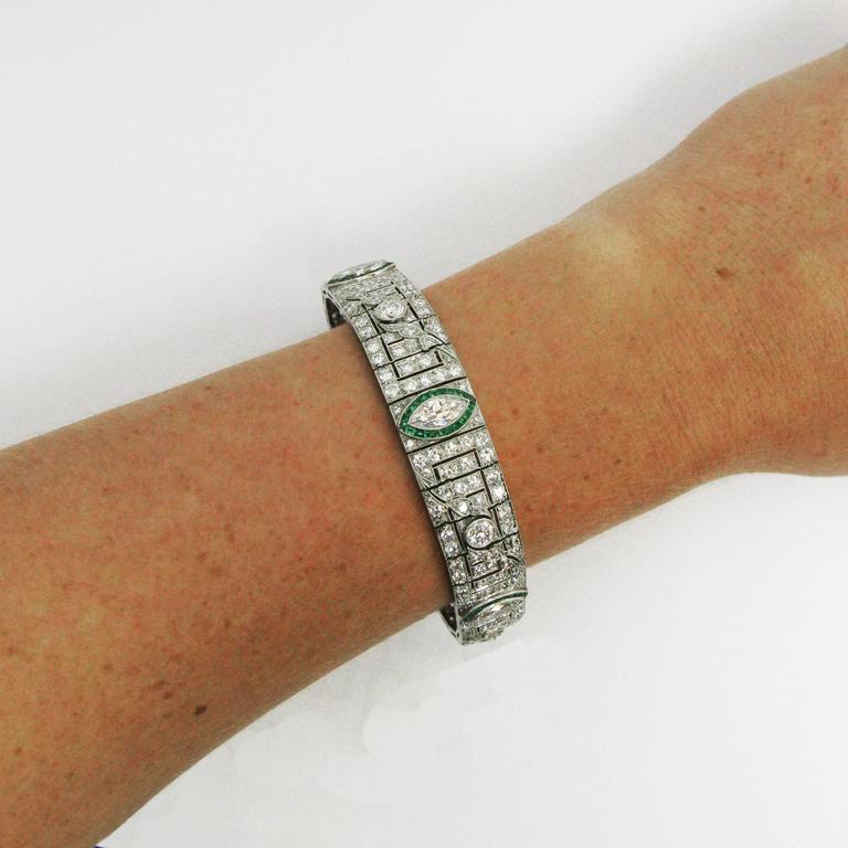 An elegant Art Deco platinum line bracelet features five graduated marquise-cut diamonds in square-cut emerald surrounds. Between each marquise diamond is a beautifully detailed, geometric plaque with a round-cut diamond bezel-set at the center of