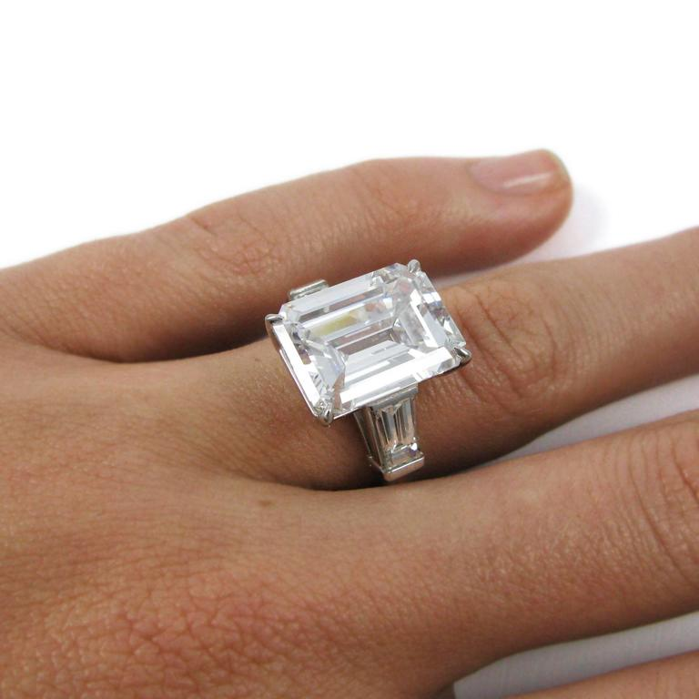 This stunning ring features a 10.01 carat emerald-cut diamond with G color and SI1 clarity. The emerald cut is flanked by two tapered baguette-cut diamonds totaling 1.35 carats in a classic platinum mounting.  Purchase includes GIA Diamond Grading