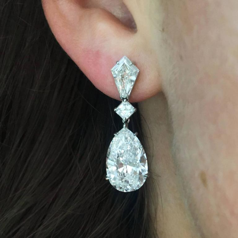 This incredible set of diamond drop earrings feature a matched pair of spectacular E color, VS2 clarity pear shape diamonds, weighing 5.01 and 5.05 carats respectively. These pear shapes are suspended from two Asscher-cut and kite-shaped diamonds.