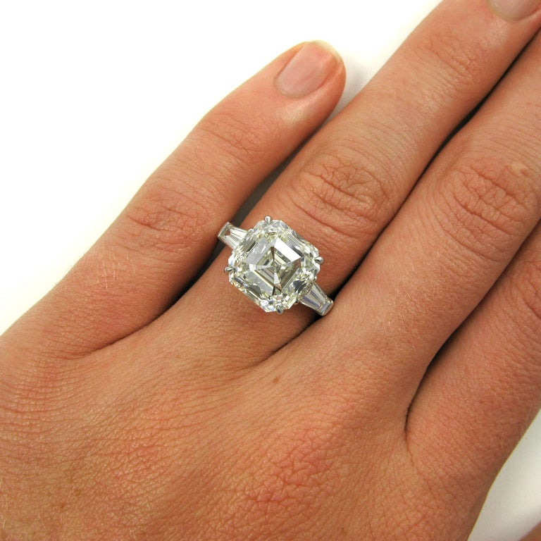 A lovely 7.00 carat Asscher-cut diamond with K color and VS2 clarity claw set and flanked by two tapered baguette-cut diamonds in an eternally classic style. The two baguettes total approx. 0.90 carat. Mounted in a J. Birnbach ring  Purchase