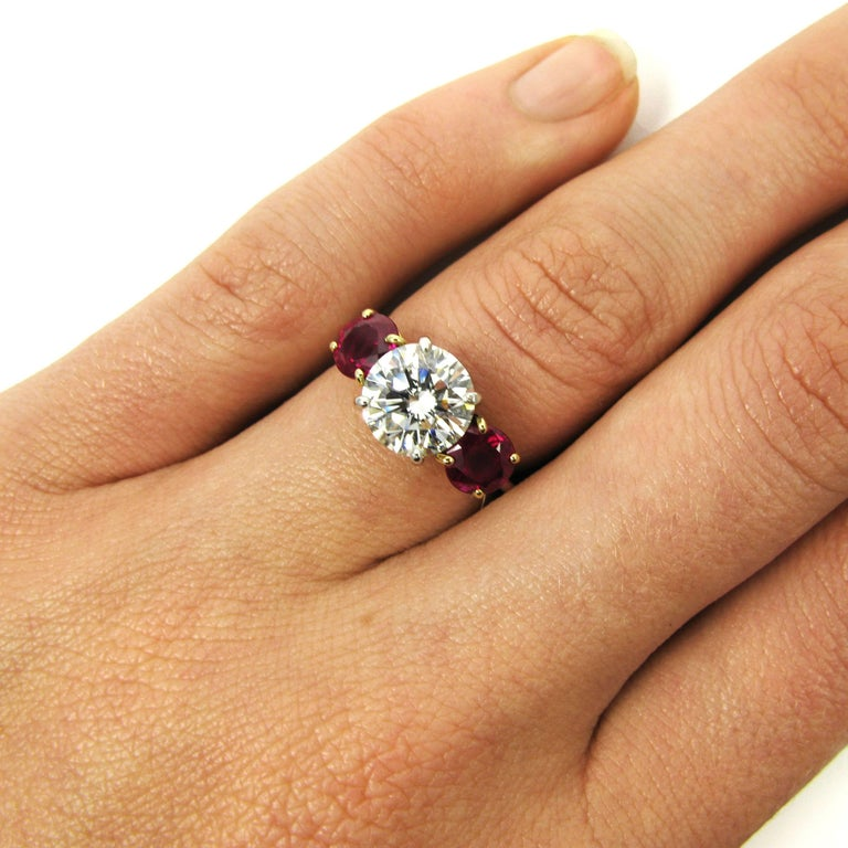 A 2.10 carat round brilliant-cut diamond I color and VS1 clarity is flanked by 2 round-cut rubies in this lovely Tiffany signed ring. Mounted in platinum and 18k yellow gold.   Purchase includes complimentary sizing, original GIA Certificate and