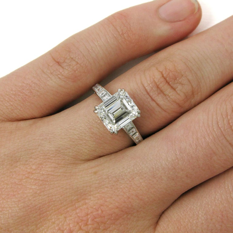 This elegant platinum engagement ring features a 3.02 carat emerald cut diamond with E color and VS1 clarity. This center stone is set atop a slightly graduated ring shank channel-set with 20 carre-cut diamond totaling approx. 0.60 carat.   Purchase