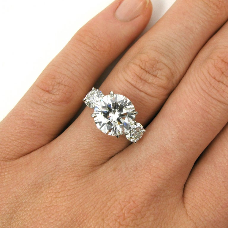 This powerful three stone diamond ring centers around a 4.11 carat round brilliant-cut diamond with H color and VS2 clarity. This center stone is flanked by two smaller round brilliant-cut diamonds totaling 1.06 carats, each with H color and VS