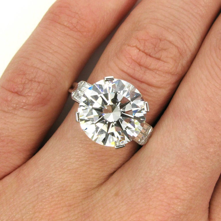 A truly stunning 7.10 carat round brilliant-cut diamond with H color and VS1 clarity. This incredible diamond has excellent cut, polish and symmetry and is set into a vintage platinum mounting accented with four straight baguettes and two half-moon