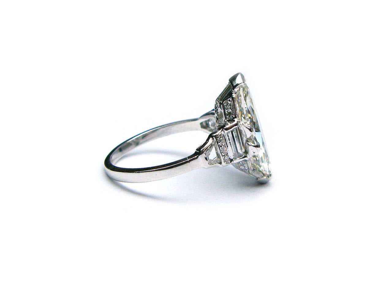 This GIA certified J color VS2 clarity Art Deco period Oval cut diamond is set in a charming platinum and diamond ring complete with baguettes and pave. This one-of-a-kind piece is perfect for a one-of-a-kind woman!