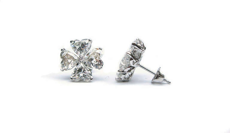 These lovely, cluster diamond earrings are set in platinum and feature eight E color, VS clarity heart shaped diamonds, with a total weight of 6.10 carats. These earrings are the perfect alternative to a simple stud. They are classic, but add a
