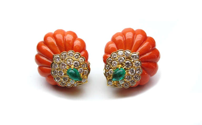 These signed David Webb coral earrings, featuring two stunning green pear shaped emeralds and 42 round brilliant diamonds set in 18 karat yellow gold are an absolute must have for the girl on the go. They are the perfect way to add some color to any