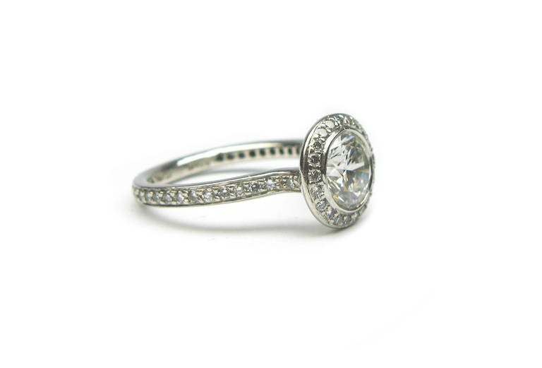 This captivating 1.01ct, GIA certified, G color, Si1 clarity, round brilliant diamond ring sits beautifully in a pave bezel setting creating the illusion of a much larger stone. The pave extends down the band of the ring adding extra sparkle. The