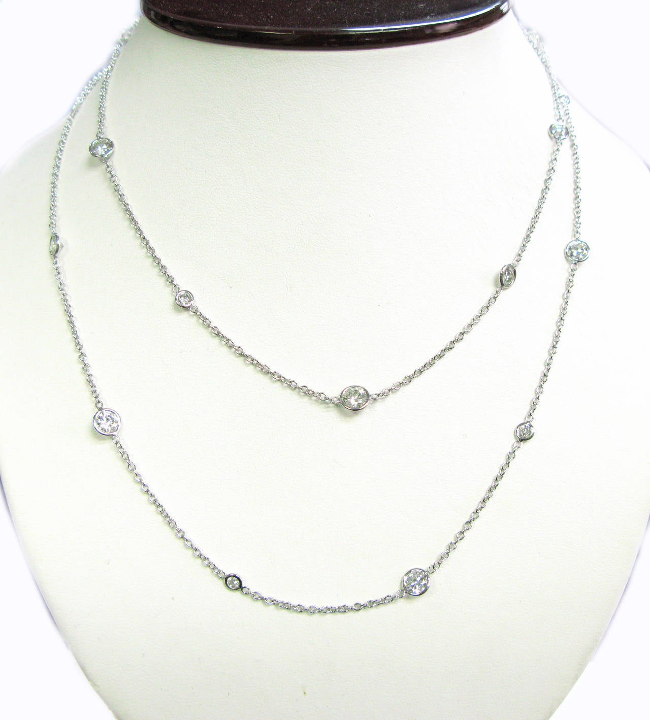 This sensational 14kt white gold handmade necklace features bezel set round brilliant diamonds of varying sizes spaced along an open link chain. There are 21 diamonds with a combined weight of 7.76cts. The necklace is 36