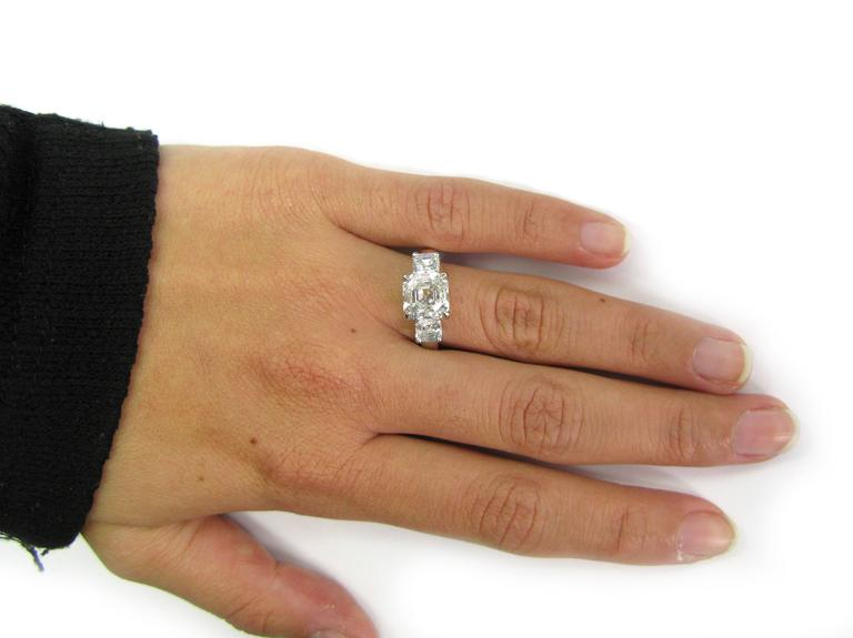 This lovely handmade platinum ring features 3.01 carat, F color, VS1 clarity, Asscher-cut diamond center stone flanked by two smaller Asscher-cut diamonds totaling approx. 0.95 ctw. This stunning piece would make a perfect engagement or anniversary