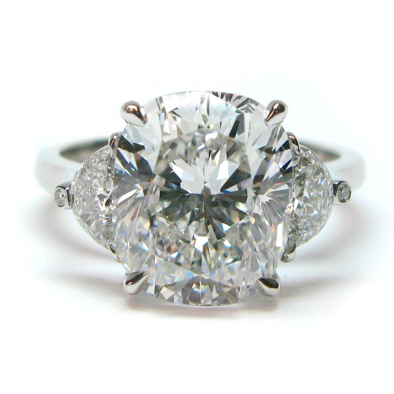 This charming engagement ring is guaranteed to set hearts a flutter... featuring a GIA certified 4.37 ct Cushion of E color and VS1 clarity flanked by a pair of half moons = 0.44 ctw. This unique setting has two brilliant round diamonds = 0.02 ctw
