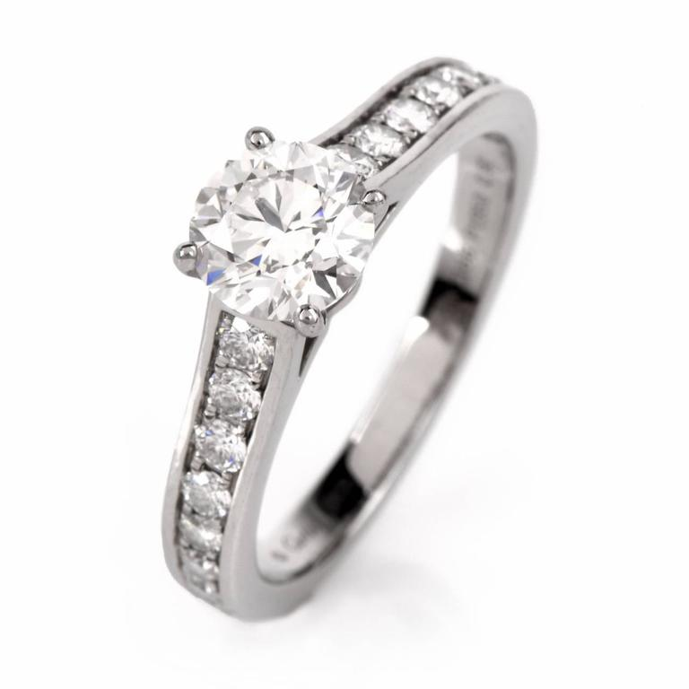 This dazzling GIA certified designer Cartier engagement ring crafted in solid platinum, Showcasing 1 genuine GIA Certified (Report # 2156222364) round brilliant cut diamond approx: 0.90cttw, H color, VVS2 clarity in prong set and measuring approx: