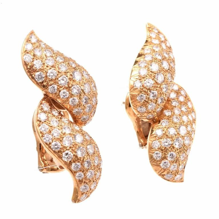 These diamond earrings are crafted in solid 18K yellow gold. Adorned with 130 sparkling round-faceted diamonds, cumulatively weighing 6.85cts, graded G-H color and VS1-VS2 clarity. These graceful diamond earrings feature posts and clip-backs for