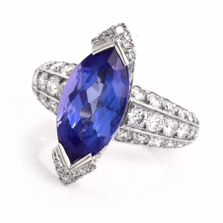 This impressive ring is crafted in solid platinum. It exposes a sizable marquise shape genuine tanzanite approx 4.39cts mounted within a diamond swathed canoe shape setting. This dazzling ring is adorned with approx.3.88cts of pave-set high quality