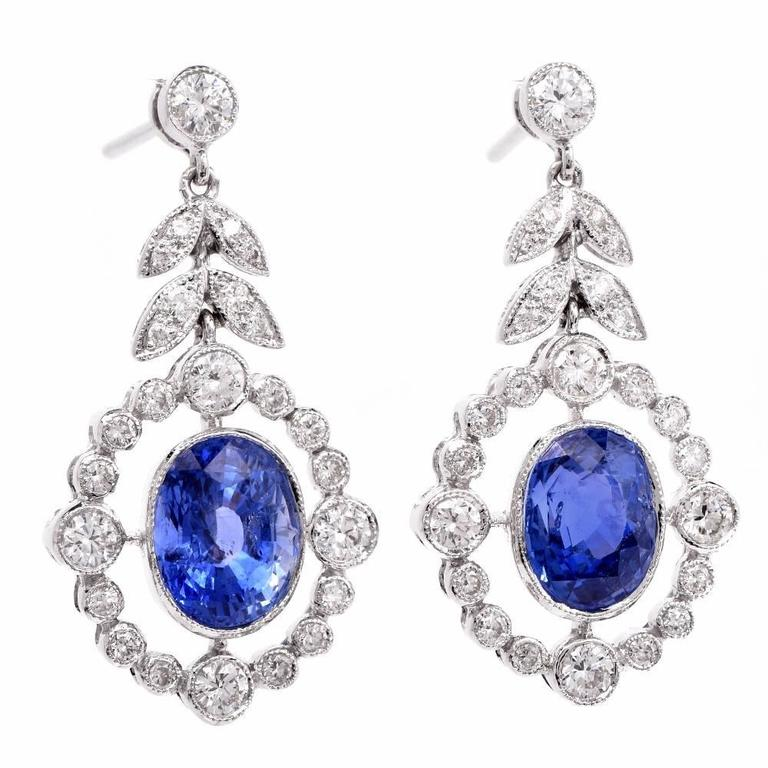 These enchanting Art Deco style estate pendant earrings are crafted in platinum and feature a pair of  genuine  oval-faceted blue sapphires cumulatively weighing 7.05 cts of a delightful cornflower blue color.  Mounted within mille-grained