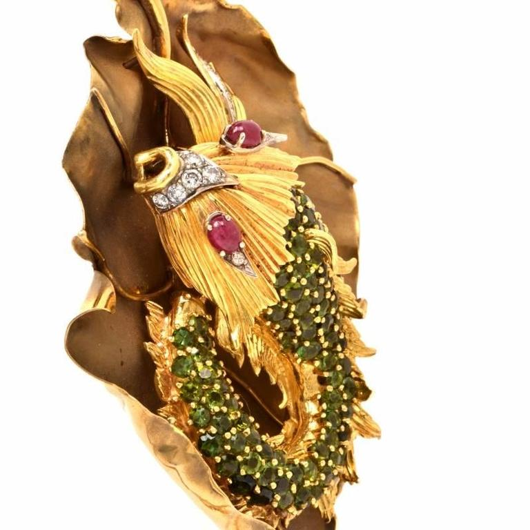 This fish  pendant is handcrafted in solid 18K yellow gold.  The large well-crafted designer pendant is showcasing a detailed fish design resting on top of a waterlilly leaf. It is covered with some 14 genuine round cut diamonds approx: 1.65 cts,