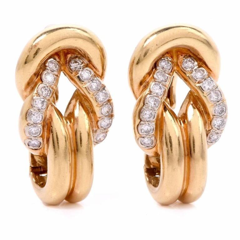 These Vintgae clip-back earrings of opulent and classically distinct aesthetic are crafted in 18-Karat yellow gold. The earrings depict at the center an openwork inverted heart profile, set  with 28 round-faceted diamonds in total. The precious