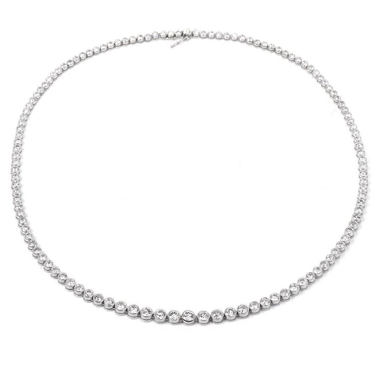 This Parrkling Vinatge Platinum diamond  Riviera Tennis necklace circa 1960's featuring 111 round brilliant cut diamonds, extra white and clean, bazel set weighing 9.50 carats G to H  color VS1 clarity eith few SI clarity.   The necklace measures