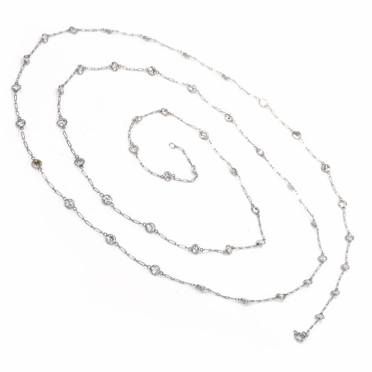 This impressive diamond by the yard necklace of considerable length is crafted in solid platinum and weighs 9.6 grams. This diamond Vintage  necklace is adorned with 50 round-faceted diamonds, bezel-set at equal intervals throughout the length of