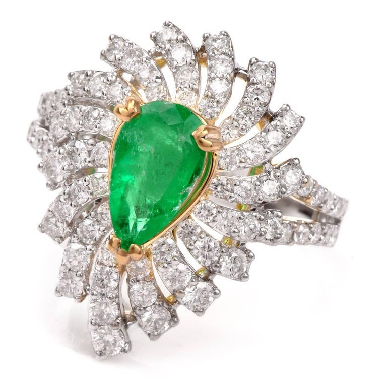 This captivating estate cocktail ring of classically sophisticated aesthetic is crafted in solid 18-karat white gold with a touch of yellow gold applied to the setting of the teardrop shape, 0.90 carat emerald positioned at the center of the
