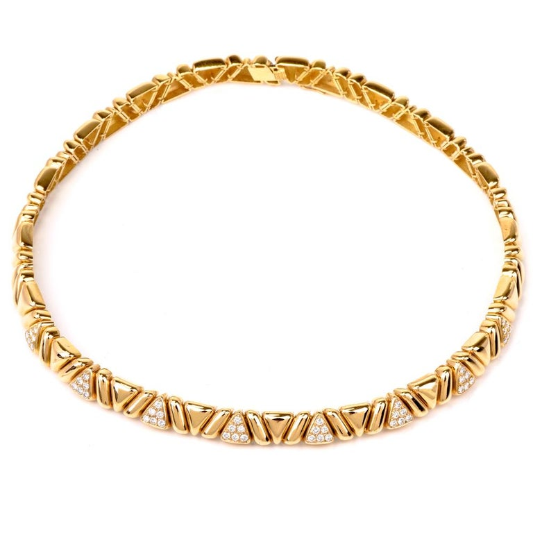 This classically elegant estate choker necklace with pave diamonds is crafted in solid 18-karat yellow gold, weighing 83.2 grams and measuring 16 inches long x 8 mm wide. The necklace incorporates an assemblage of tri-dimensional,