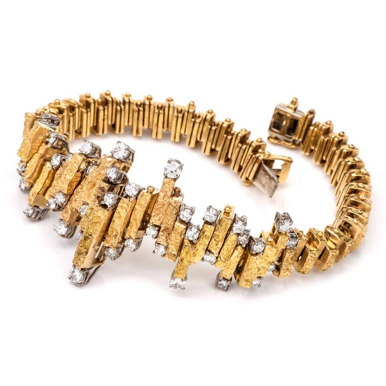 This alluring vintage bracelet of unmatched feminine grace is crafted in 18 karat yellow nugget gold which embellish the borders of the central zig-zagged décor of bracelet. The 42 round-faceted diamonds weigh collectively 2.10 carats and are graded
