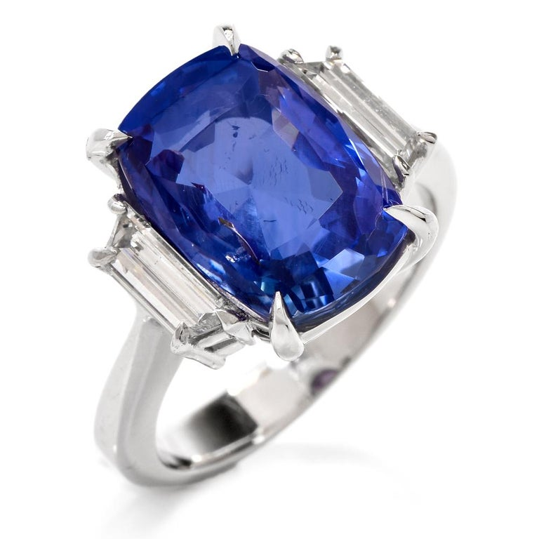 This high-quality  three stone sapphire and diamond ring is handcrafted in solid platinum. Displaying a prominent  cushion-cut natural No Heat genuine  blue sapphire with GIA lab report weighing approx. 9.07 carats and measuring 13.28 x 9.41 x