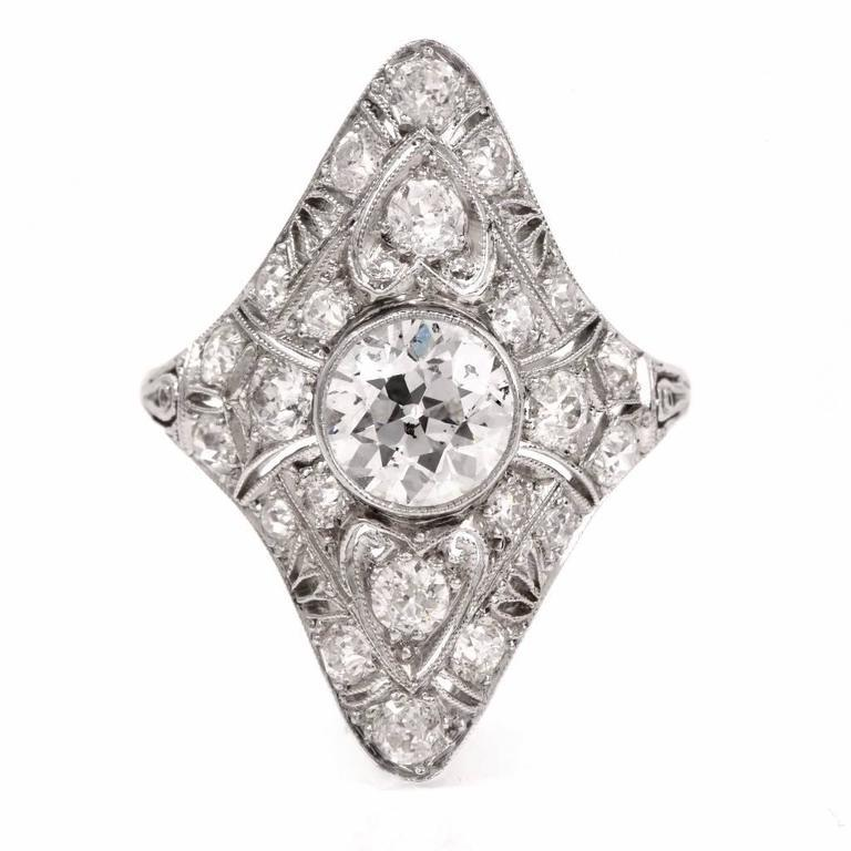 This classically Antique Art Deco diamond ring is crafted in solid Platinum depicting filigreed profiles. The ring is centered with a prominent 1.35cts brilliant-cut diamond, graded E-F color and SI1-SI2 clarity (small inclusion under table hardly