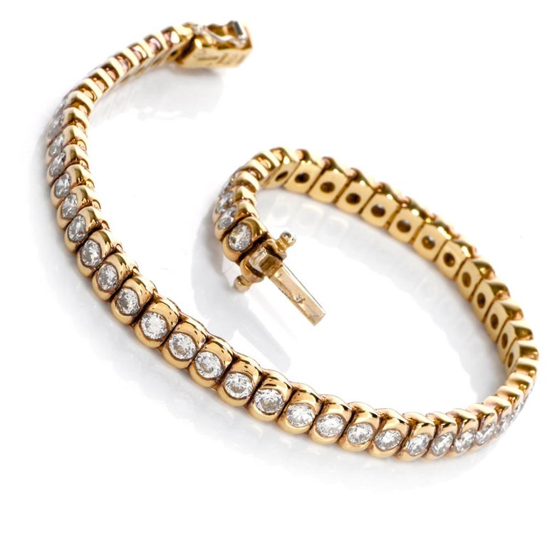 This extremely well-made diamond tennis bracelet is crafted in solid 18 karat yellow gold, weighs 21 grams and measures 7 inches long. It comprises 53 flexible links, each securely channel set with a high-quality round-faceted diamond weighing