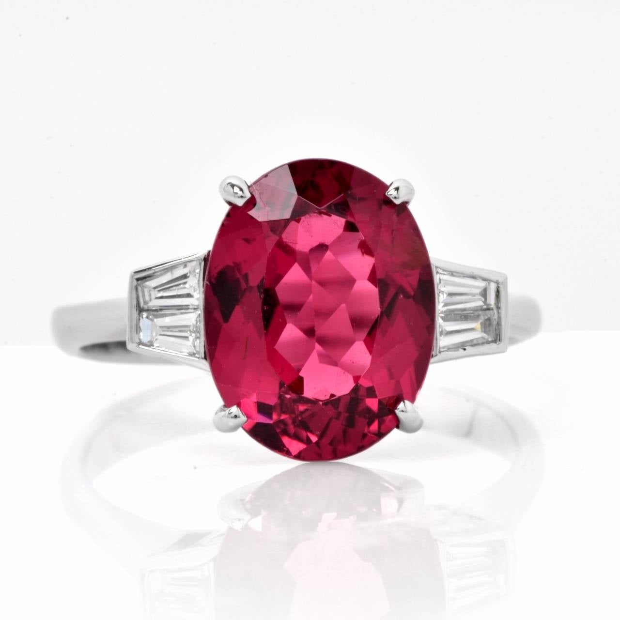 This vivacious diamond and pink tourmaline estate ring is crafted in solid 18K white gold, weighs approx. 4.00 grams  and measures 10 mm wide and 7 mm high. Designed with simplicity and timeless elegance, this ring exposes an oval-faceted  3.39 ct