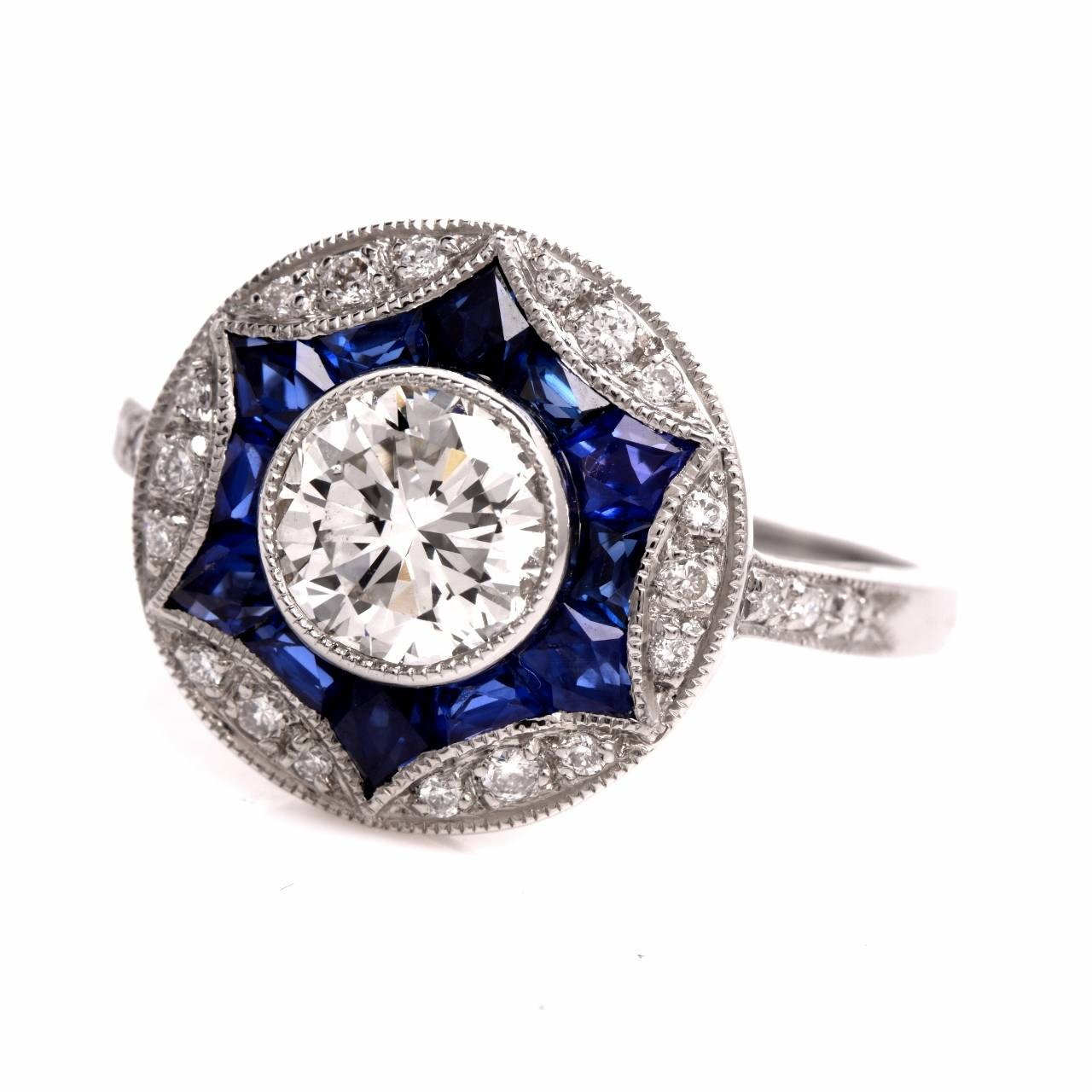 This conspicuous  diamond and sapphire engagement ring of unsurpassed refinement is crafted in solid platinum, depicts a finely mille-grained, color-contrasting orbicular  plaque, exposing at the center an eye-catching  0.95ct outstandingly