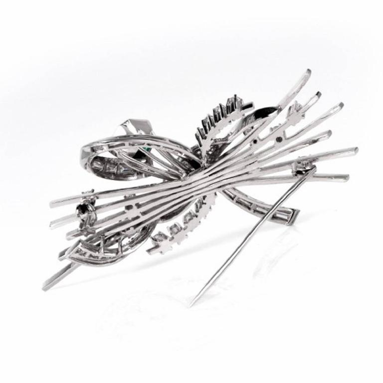 This 1960's  enchantingly refined diamond and emerald  brooch of naturalistic inspiration is immaculately handcrafted in solid platinum. It is designed as a floral bouquet with an eye-catching extremely high quality genuine emerald-cut emerald
