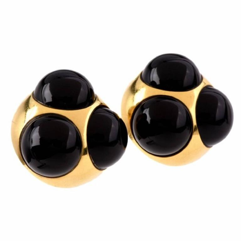 These Tiffany & Co. Paloma Picasso earrings are crafted in solid 18K yellow gold, weighing 35.1 grams and measuring 24 x 10 mm. in bold and sculptural Retro style, these earrings incorporate orbicular plaques each depicting a trio of black onyx