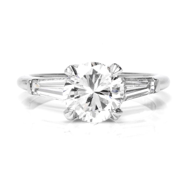 This classic  diamond engagement solitaire ring  is crafted in solid  platinum.   Centering a certified round brilliant cut diamond approx: 1.53cttw, H color, VS1 clarity in prong set.  This classic ring set with tapper baguette  cut diamonds