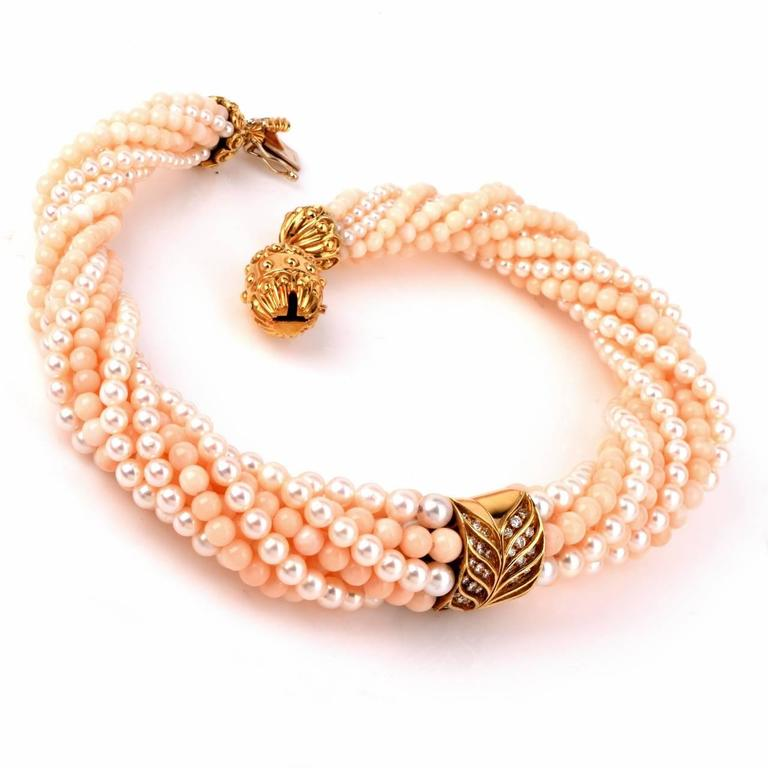 This estate retro choker necklace and artistic craftsmanship incorporates5 strands of graduated angel skin color natural genuine coral beads intertwined with 5 strands of graduated lustrous genuine pearls. An enchanting 18K yellow gold central
