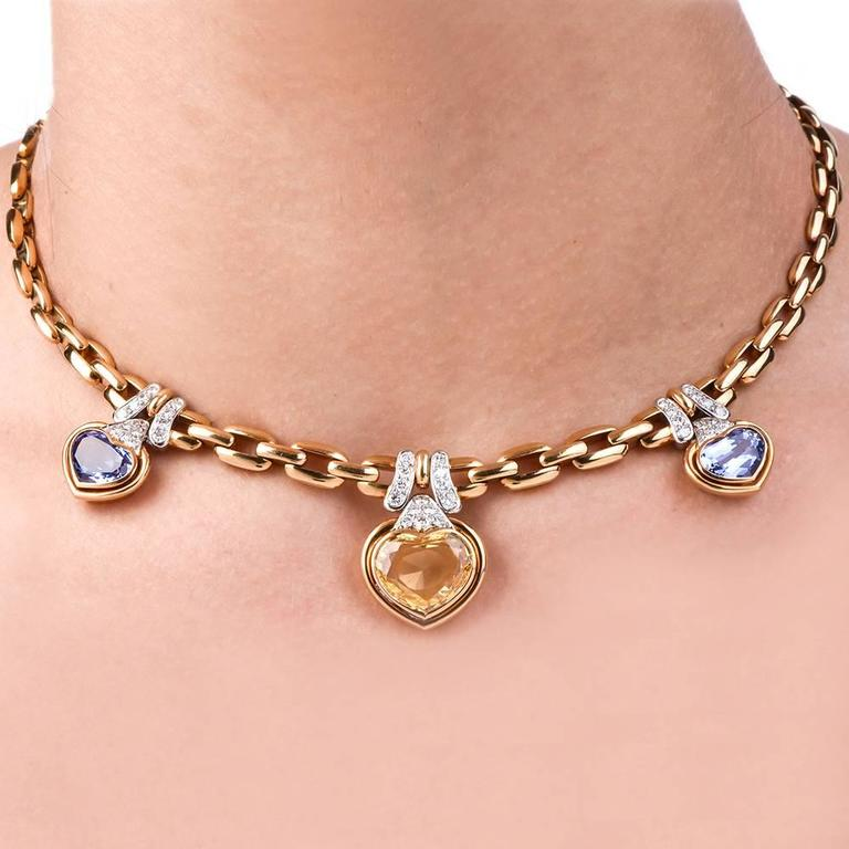 This extremely well crafted diamond sapphire Italian necklace is made in 18K yellow gold, adorned with three heart pendants set with three heart shape genuine yellow and blue sapphires. All 3 sapphires are certified by GIA lab to be natural  without