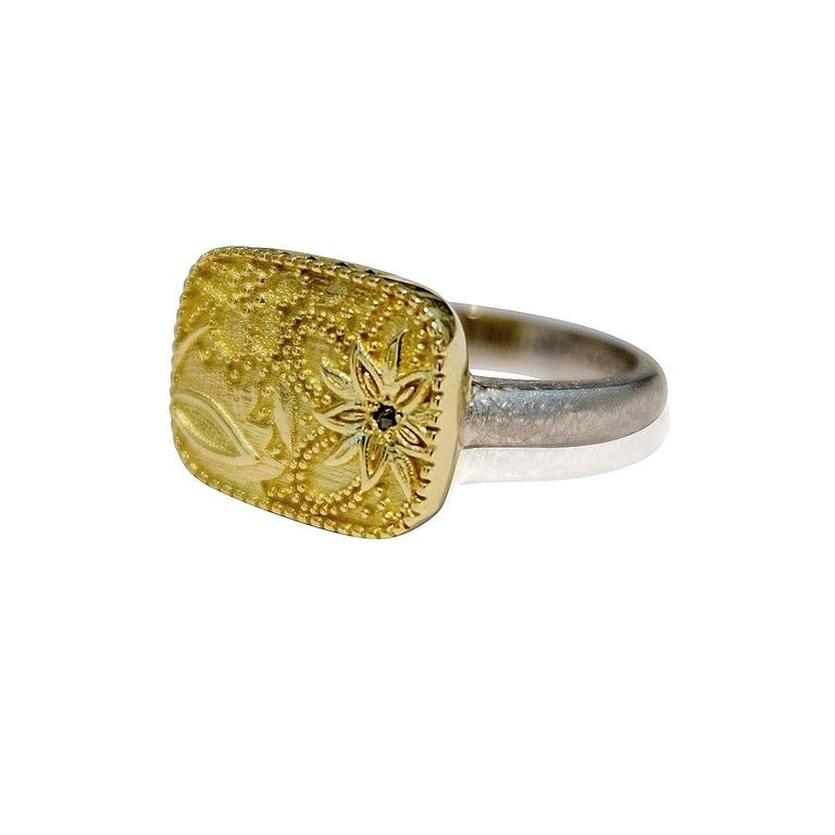 Ebon Jardin  This gorgeous ring has an ornate flower design in relief upon the 18ct yellow gold rounded square setting. A single black diamond has been bead set in the centre of the main flower and four other black diamonds have been set on the