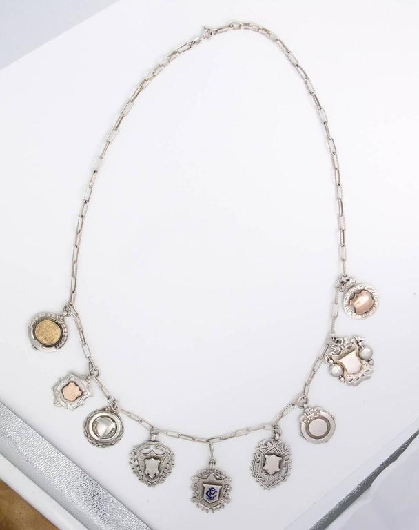 Very unusual sterling chain necklace with nine sterling pendants from England. Many were given as prizes given at various competitions. all hallmarked with silver makers. names. Ca. 1897-1940's England