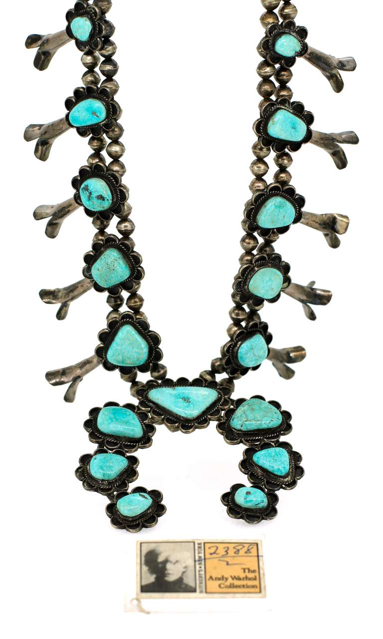 Navajo Squash Blossom necklace in silver set with turquoise, decorated with silver charms, the central piece an open circular pattern. Provenance: personally belonged to Andy Warhol, Sotheby's 1988 sale, Dimensions 69 x 9cm (190,5grs)