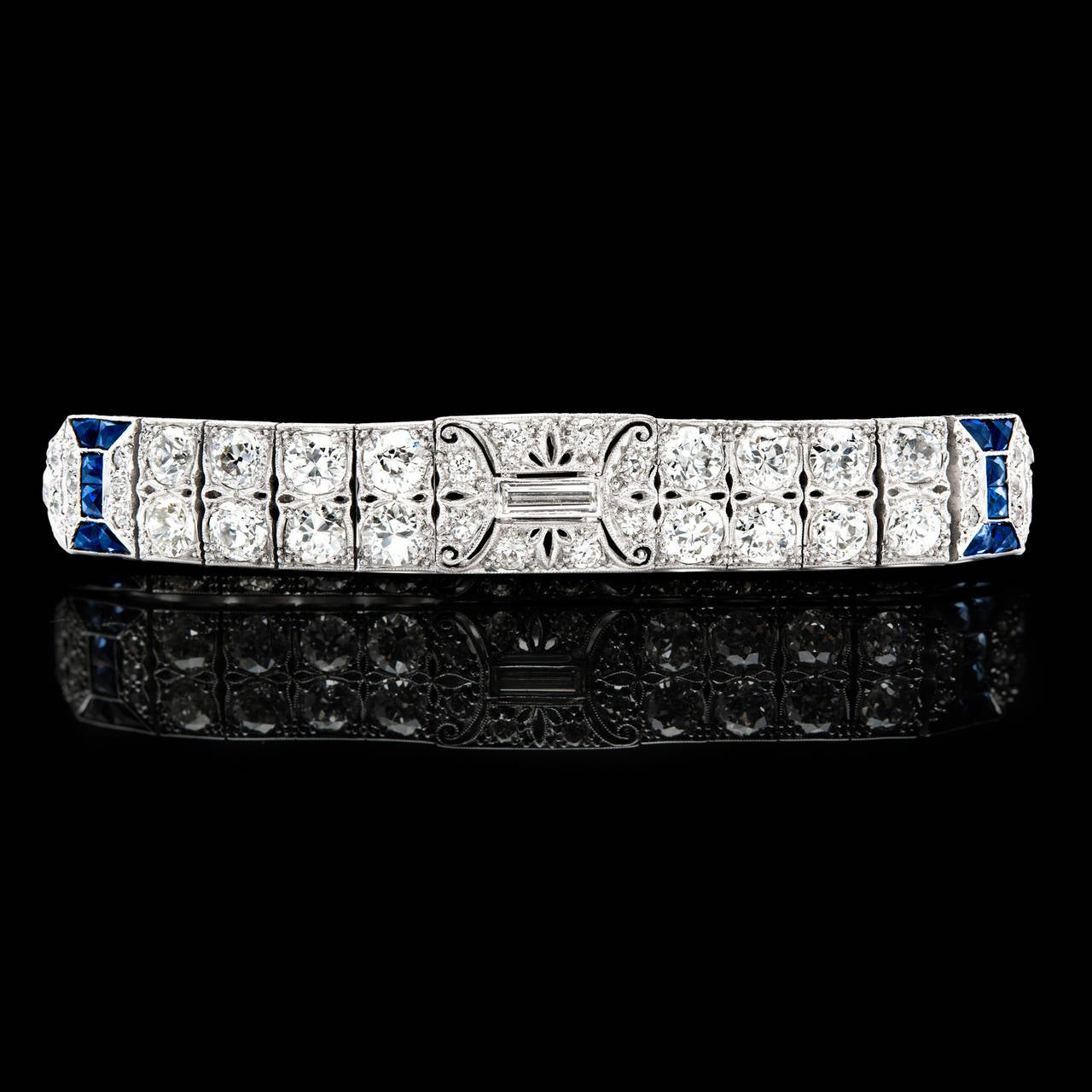Hand Engraved Art Deco Diamond & Sapphire Bracelet Features 54 Old European and rectangular step cut Diamonds weighing a total of approximately 8.29 carats accented by 12 French and calibre-cut synthetic Blue Sapphires. The platinum is detailed in