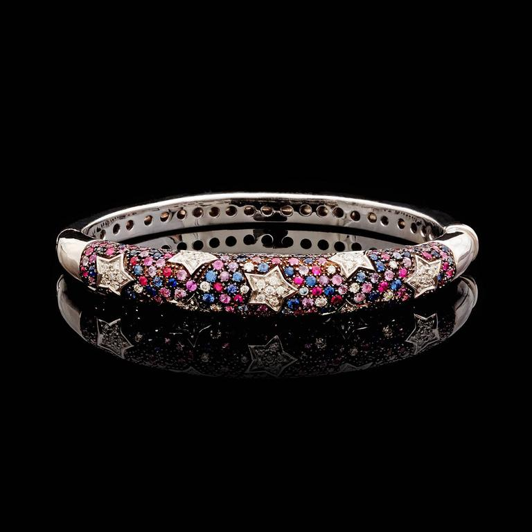 Salavetti 18k white gold bangle bracelet pavé-set with 3.30cttw of round brilliant-cut pink and blue sapphires and 0.64cttw of G-H/VS quality diamonds set in a star pattern. The bangle has a 6 inch circumference; the width tapers from 9.0 to