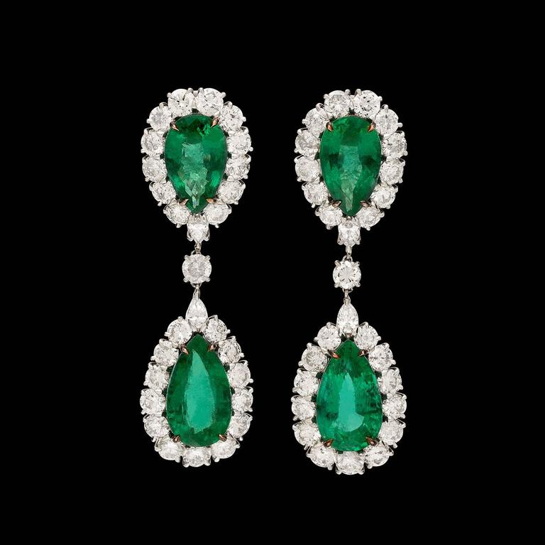 Show-stopping 18k white gold drop earrings designed with 4 pear-shaped emeralds weighing in total 24.48 carats, with round brilliant-cut and pear-shaped diamond surrounds. Total diamond weight is 11.40 carats. The earrings weigh 20.1 grams, and