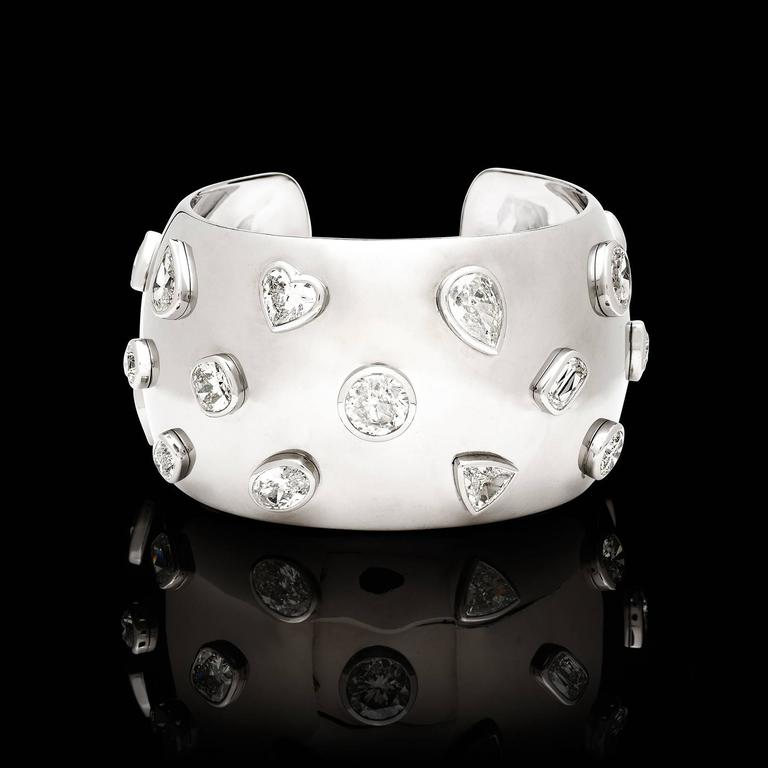 This wide, palladium cuff bracelet adorned with 20 various bezel-set fancy and round brilliant-cut diamonds, weighing in total 27.93 carats, is a one-of-a-kind showstopper! The bracelet is 1 5/8 inches wide, and weighs 134.5 grams. Accompanied by 11