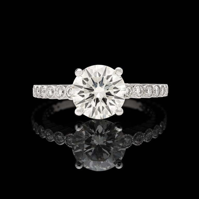 Handmade in France, this gorgeous custom Platinum mounting highlights a stunning 2.06 carat GIA graded L/VS2 Round Brilliant Cut Diamond flanked by 26 round diamonds for an additional 0.38 carats. This lovely center stone has exceptional sparkle and