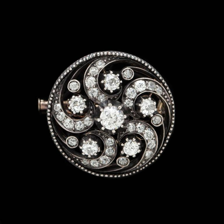 Beautifully crafted swirl motif Diamond Pin featuring approximately 2.25 carats of impressive round diamonds. 36 diamonds are expertly set in a combination of 14 karat yellow gold and silver construction, as was common for the period. The piece